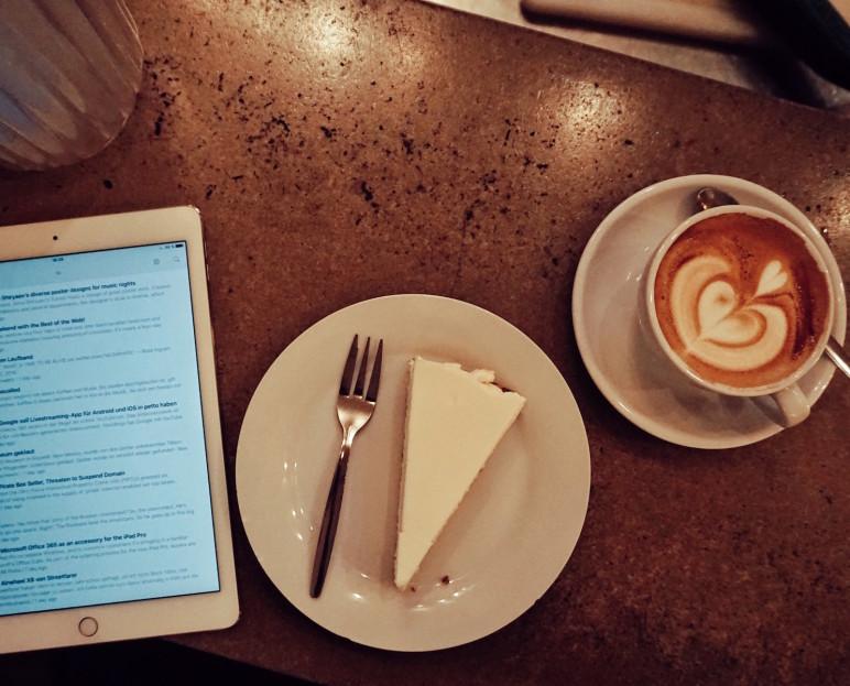 iPad mit Kuchen und Flat White